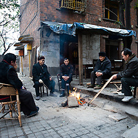 CHONGQING - JAN 18 2011: neighbours sit by the fire in a cold afternoon in the Jiulongpo district. They are the last remained living in the building  behind them that will be soon razed down to rise new buildings.