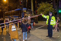 Victoria Embankment, London, January 19th 2017. Following the discovery of an unexploded bomb in the river Thames near the Houses of Parliament, Police hold up their cordon to allow a party of tourists to board their coach after it had become trapped within the exclusion zone.