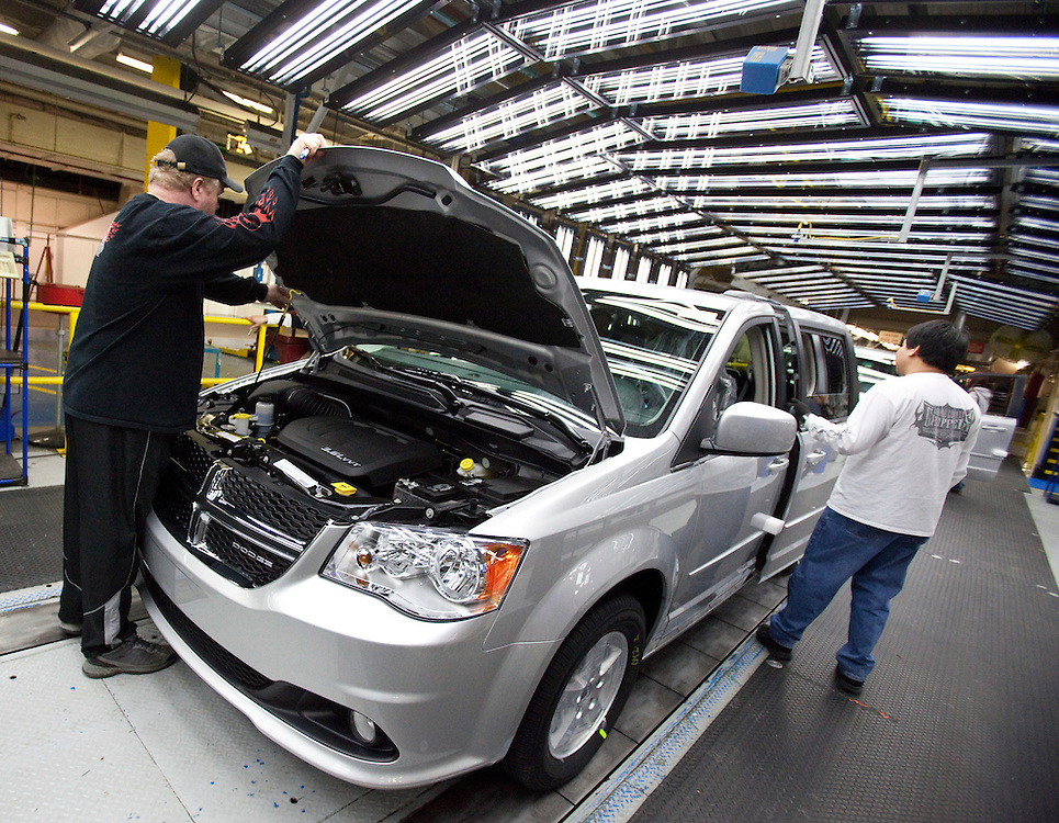 Workers on the production line at Chrysler's assembly plant in Windsor, Ontario, do final inspection on one of their new minivans as the company celebrated the production launch of the new Dodge Grand Caravan and Chrysler Town and Country, January 18, 2011.<br /> The Canadian Press/GEOFF ROBINS
