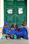 Three women chatting on a door step, Uyuni, Potosi, Bolivia