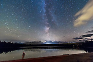The Milky Way over Lake Annette in Jasper National Park, Alberta, a Dark Sky Preserve. I shot this at the Lake Annette Star Party, one of the Dark Sky Festival events, using the Canon 60Da and 10-22mm lens at 10mm f/4 and ISO 3200 for 1 minute, untracked. Shot October 24, 2014 with fresh snow on Whistler across the lake and valley and on a calm night with still waters reflecting the stars. A photographer participating in the photo workshop is shooting back toward the star party.