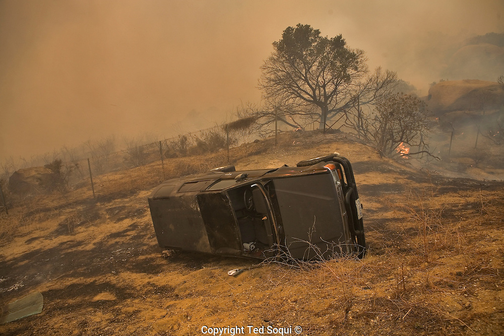 A car that crashed and overturned on the 118 freeway due to the freeway..Wild fires near Porter Ranch and Simi Valley. Over 5000 acres burned with several houses burning. 60 mph Santa Ana wind event stoked the brush fires and are expected to blow all week long.