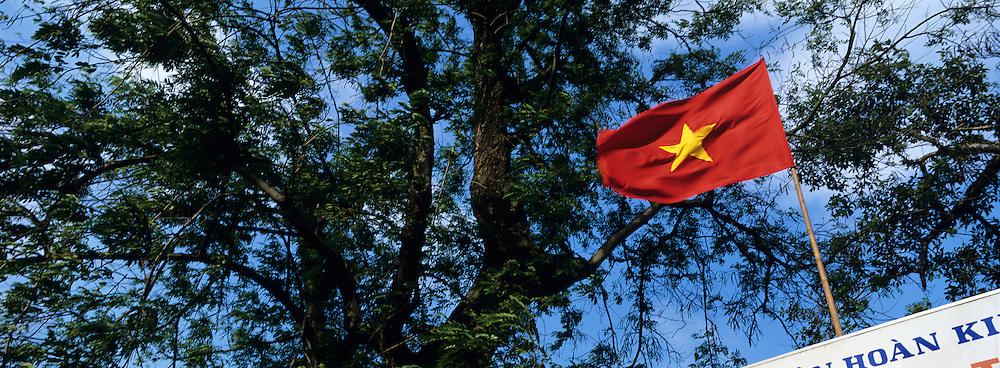 Asia, Vietnam, Hanoi, Vietnamese flag flies above tree-lined Hoan Kiem Lake in city's Old Quarter