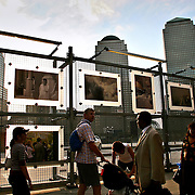 Tourists and passersby view photo exhibit about 9/11 at Ground Zero, NYC.  9/7/06.