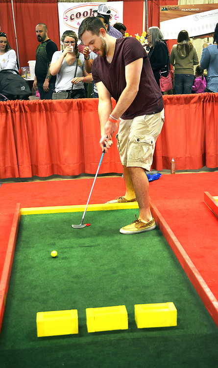 gbs032617d/ASEC -- Carlos D. De Sanctis of Albuquerque putts a hole-in-one at the miniature golf course in the New Mexico Pinon Coffee booth at the Southwest Chocolate & Coffee Fest at the Expo NM State Fairgrounds on Sunday, March 26, 2017. Sanctis won a bag  of coffee for two hole-in-ones. (Greg Sorber/Albuquerque Journal)