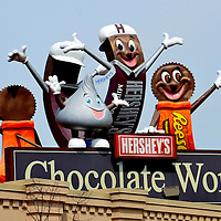 Hershey's Chocolate World Entrance Characters in Hershey, Pennsylvania <br /> When the Swiss invented milk chocolate in 1875, it was an expensive luxury with a short shelf life. That changed in 1899 when Milton Hersey developed a process to mass produce the delicacy. He then built a plant and town now called Hersey, Pennsylvania. This facility produces the branded syrup, Kiss, Mr. Goodbar, Krackel and later acquired Reese&rsquo;s and Twizzlers.  In 1973, Hersey&rsquo;s Chocolate World opened as an amusement park. The attraction offers rides, a tour of the chocolate making process and, of course, a haven for kids in a candy store.