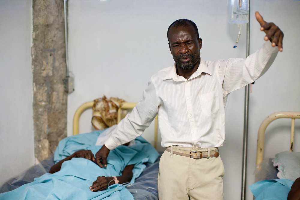 A man prays for cholera patients at the Hospital Albert Schweitzer on Thursday, October 28, 2010 in Deschapelles, Haiti.