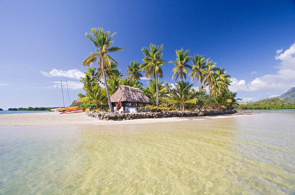 Clear water, white sandy beach and palm trees on a small tropical island in Fiji.