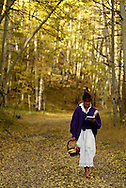 Woman reads while walking to picnic in San Juan National Forest, Colorado, autumn, <br /> MODEL RELEASED