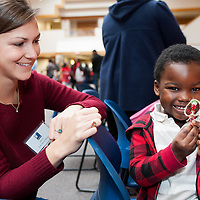 A volunteer makes decorations with a child at the Goodwill Holiday Party at Goodwill headquarters in Roxbury.