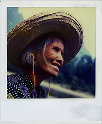 Polaroid SX70 portrait of an old chinese woman wearing a large hat. Guangxi province, China, Asia.