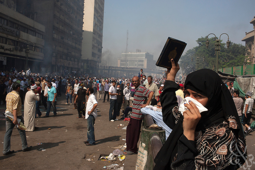 "An Egyptian woman holds a Koran aloft amid tear gas and smoke as intense street clashes take nearby around Ramsis Square during the August 16, 2014 ""Day of Rage"" protests in Cairo, Egypt."