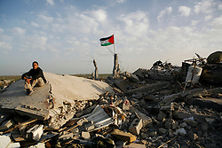 A boy sits atop his home destroyed by Israel in Jabaliya in the Gaza Strip.