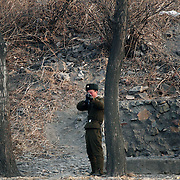 A North Korean soldier points a gun to a photographer in the bank of the Yalu river in Sinuiju, North Korea, on Wednesday, Feb.  9, 2007. As The Six Party talks resume in Beijing the US envoy is ompimistic on North Korean nuclear talks.
