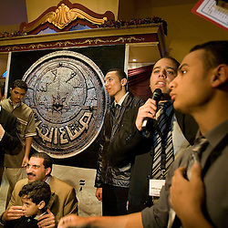 Amr Khaled, an Islamic televangelist, is seen posing for photos with his followers at a Life Makers gathering inside a local wedding hall, Alexandria, Egypt, Dec. 24, 2005. The former accountant with the Western-style suit and soft voice had previously been asked to leave Egypt as his revival gained strength. As a result he started preaching on several television shows, turning him into an international celebrity.