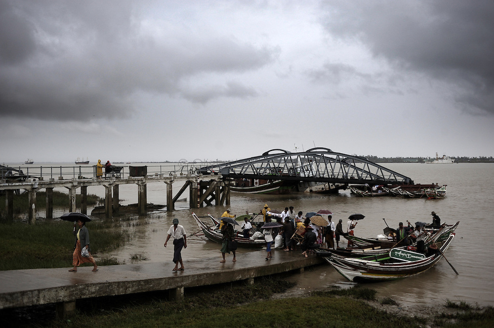 People disembark on the Yangon's harbour destroyed by cyclone Nargis after crossing the river on May 15, 2008. State television on May 16, 2008 put the latest toll at 77,738 dead and 55,917 missing from Cyclone Nargis, which barrelled into the country on May 2-3, wiping away entire villages and submerging swathes of land under flood waters.