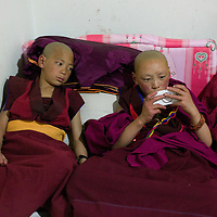 APRIL 4, 2012 :  young Tibetan monks play with mobile phones and other electronic devices in a dorm in Xiahe.