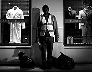 Part of a series of photos from a photo essay entitled 'Early Birds'-A look at Night Workers in the City of London..1.00am. Eric Darko-Mensah, an employee with The Corporation of London's Street Cleansing department, outside a Hackett gentleman's clothes store on Philpot Lane, London. Eric arrived from Ghana in 1973, started working for the council in 1986, moving to nights in 1986, where he has worked ever since. He is married with 3 children, and lives in Clapham, South London. His shift is from 9.30pm to 6 am..Photo©Steve Forrest