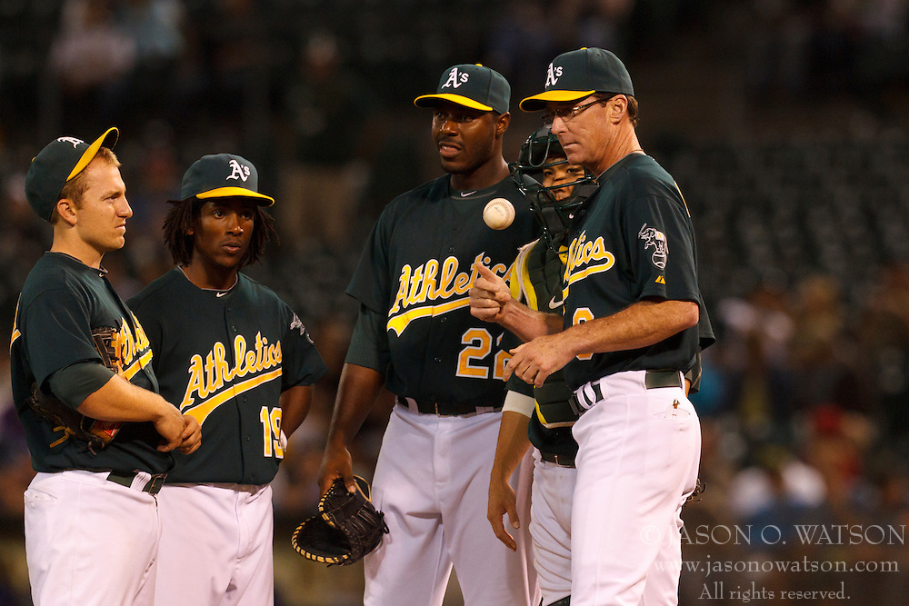 September 20, 2011; Oakland, CA, USA;  Oakland Athletics manager Bob Melvin (right) stands on the pitchers mound with catcher Kurt Suzuki (second from right), first baseman Chris Carter (center), second baseman Jemile Weeks (second from left) and shortstop Cliff Pennington (left) while making a pitching change against the Texas Rangers during the eighth inning at O.co Coliseum.
