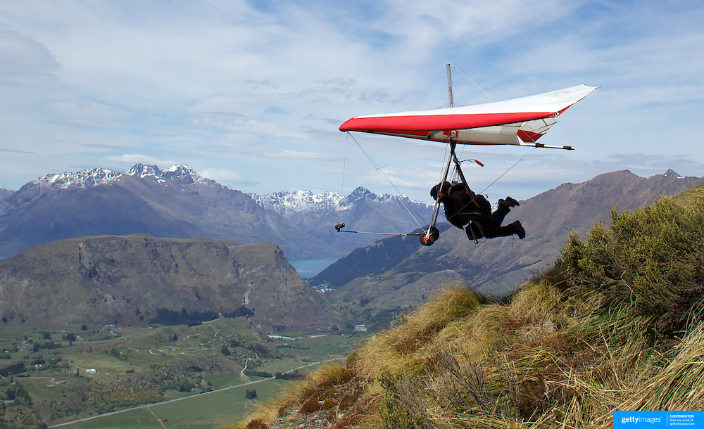 Hang Glider pilot Angus Tapper takes off with tpurist Arjun Sharma from New York during a tandem Hang Glider flight from Coronet Peak, Queenstown, New Zealand. 7th November, 2011