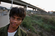 A drunk Burmese man walks along the Thai border side in the Moei River on December 22 of 2006, near Mae Sot, Thailand. On the background is the bridge and the official entry to Burma..The area has problems with alcohol and drugs smuggled into Thailand from Burma..Ethnic minority people sell burmese goods, and fish, crabs and plants collected from the Moei River in Thai border side.They live along the Moei river in between both borders..Burma has since 1962 been ruled by dictator Burman Regimes. Pro democrats and minority ethnics have since been object of human rights abuses and armed minority groups has appeared bringing a state of Civil War..This situation makes every days people to flee their villages to go to Thailand.
