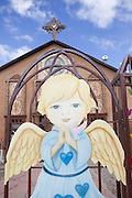 large painted angel in front of a church in Chimayo, NM