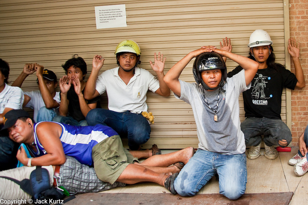 14 MAY 2010 - BANGKOK, THAILAND: Anti-government protesters signal their surrender to Thai troops who attacked the protesters with rifles and shotguns. Thai troops and anti government protesters clashed on Rama IV Road Friday afternoon in a series of running battles. Troops fired into the air and at protesters after protesters attacked the troops with rocket and small homemade explosives. Unlike similar confrontations in Bangkok, these protesters were not Red Shirts. Most of the protesters were residents of nearby Khlong Toei slum area, Bangkok's largest slum area. The running battle went on for at least two hours.   PHOTO BY JACK KURTZ
