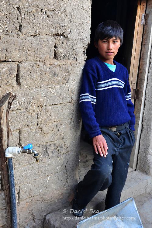 Quechua boy in doorway in Vacas, Cochabamba, Bolivia