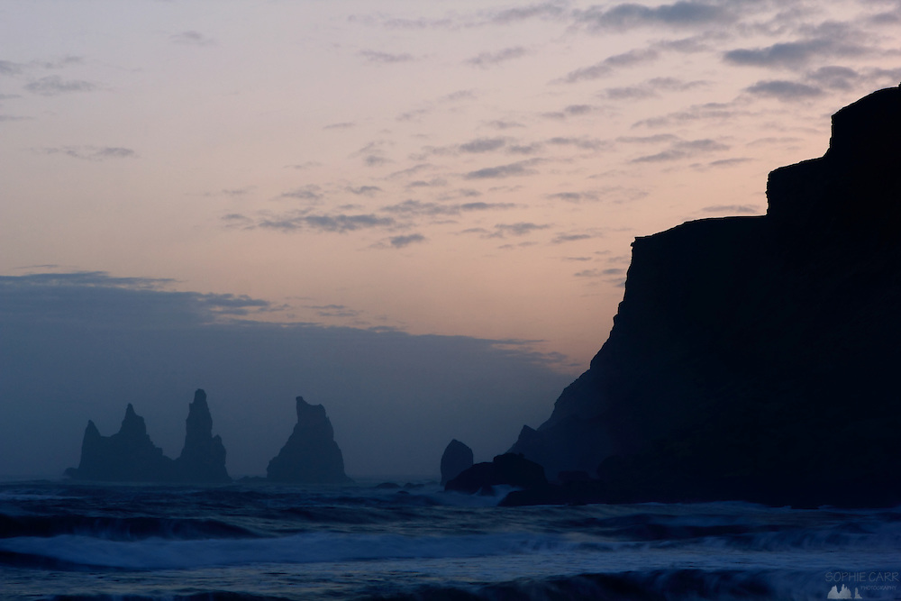 The beautiful volcanic black sandy beach at Vik - with sea stacks in the distance - along Iceland's southern coast, taken at dusk in March.