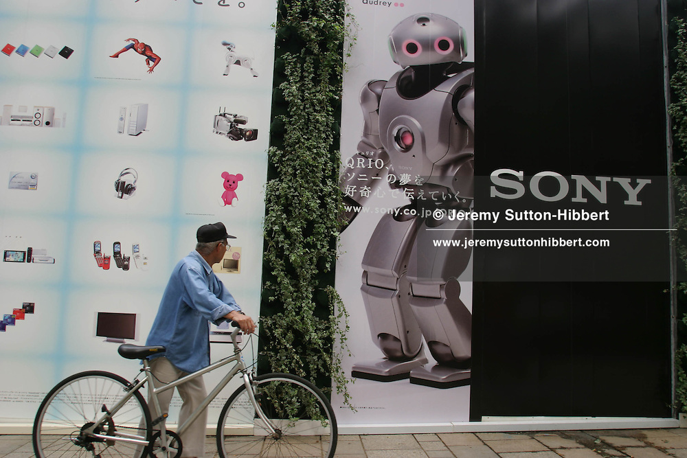 A cyclist passes an advertising board displaying products by Sony, including the Qrio robot, in the popular up-market fashionable shopping district of Omotesando.