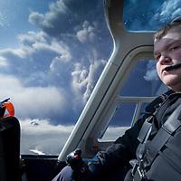 Iceland, Hvolsvelli,  Reynir Petursson pilots helicopter near massive clouds of volcanic ash erupting from summit of Eyjafjallajökull Volcano