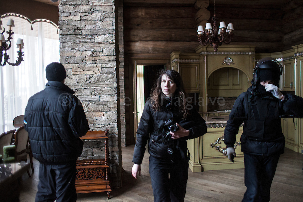 A group of Maidan activists led by journalist Tetyana Chornovol (C) visit a lavish log house belonging to multimillionaire businessman Sergey Kurchenko in search for documents connecting his business to former Ukrainian President Viktor Yanukovych family. The guarded house is located 100 km south of Kiev on the Dniepr bank. 25 February 2014.