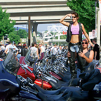 Serena Caldwell takes a picture held by Mike Groves, both of Kokomo, IN on Groves 2001 Softail Night Train at the 100th anniversary party of the legendary American motorcycle company Harley-Davidson in Milwaukee August 28, 2003. The firm begins it's four-day celebration beginning today. REUTERS/Rick Wilking