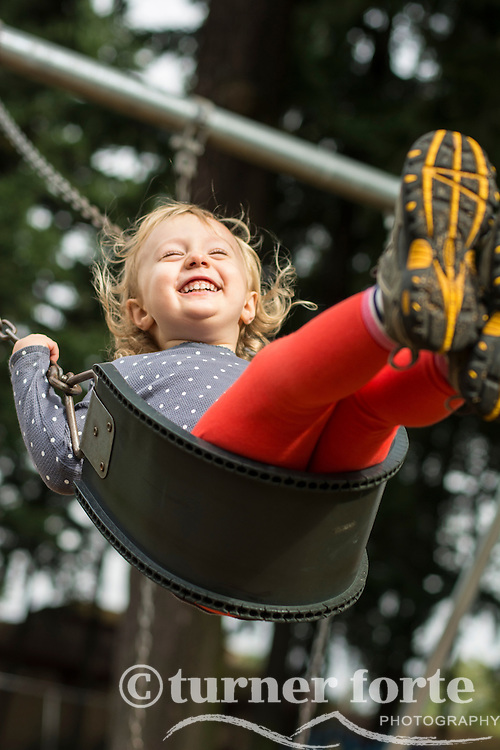 Elated toddler girl swinging high at playground in Portland, Oregon.