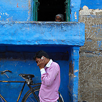 A man talking on his mobile while an old woman can be seen relaxing in her home in the background, Jodhpur, Rajasthan.