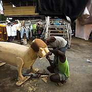 Coffin makers Dennis Adjei (in green) and Daniel Kofi work on a tiger-shaped coffin, ordered for an important head of family, at the Hello Design Coffins shop in Teshie, on the outskirts of Ghana's capital Accra, on Tuesday December 9, 2008.