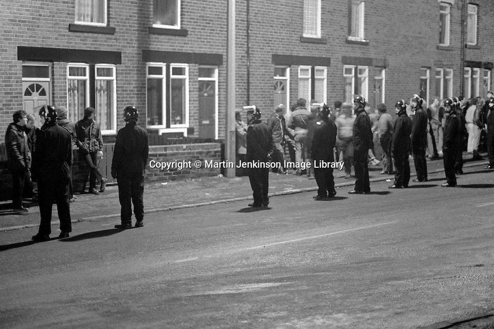 Police in riot helmets line the street in Grimethorpe at night. 16/11/1984.