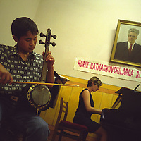 Young music student practices playing the 'dutar', an Uzbek musical instrument, in the Boris Nadezhdin  Music School in Tashkent. Tashkent was one of the main cities on the old SIlk Road trading route through Central Asia. Uzbekistan.