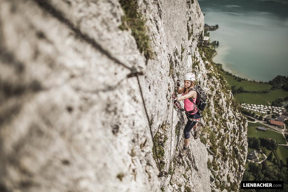 young woman climbs a via ferrata in Mondsee/Austria