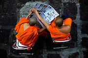 One novice monk shares his newspaper with another outside their quarters at the Marble Temple in Bangkok, Thailand.