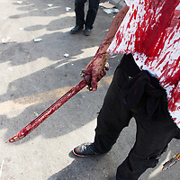 A shiite muslim man, carrying a traditional sword and knife, covered in his own blood, during the Day of Ashura in Nabatieh, Lebanon. Wounds were self-inflicted. During Ashura Day, some shiite muslims practice the ritual of self-flagellation to mourn the death of Husayn Ibn Ali, grandson of the prophet Mohamed.