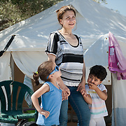 Noon, Friday 11th of September 2015. Aysha holding Sham (3½) and Bisan (2½) outside the tent where they spend the previous night in Kara Tepe camp in Lesbos island.