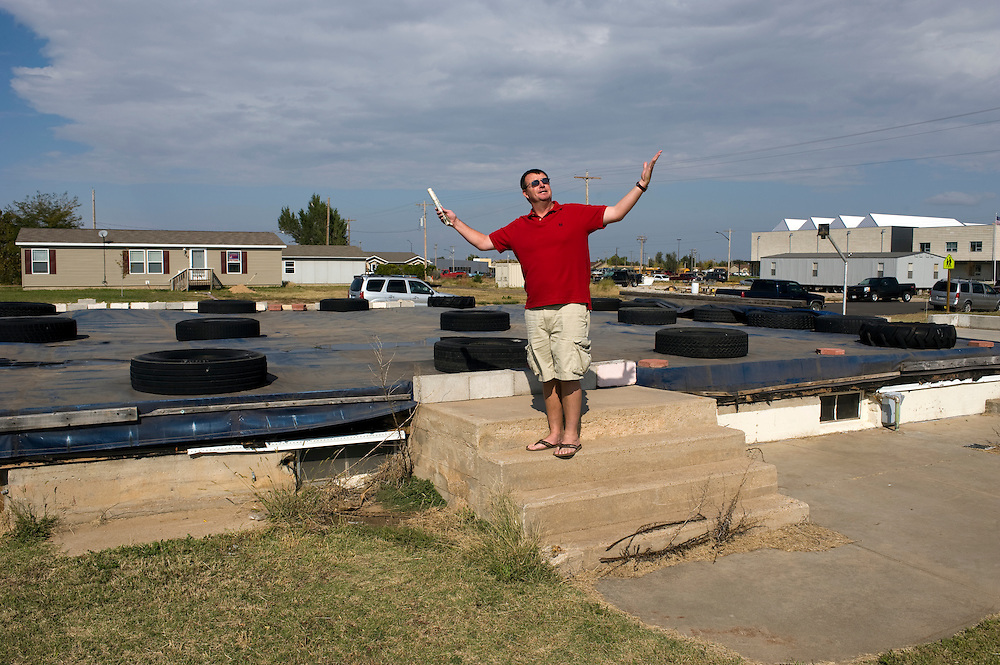 """Greensburg, Kansas, USA..Matt Deighton stands on top of the stairs of a destroyed building, he survived the tornado in its basement...""""Greensburg: Better, Stronger, Greener!"""".On May 4, 2007, an EF5 tornado cut a 1.7-mile path of destruction through Greensburg, Kansas. Winds reaching speeds of 205 miles per hour uprooted trees, demolished homes and leveled the town. Eleven people died and 95% of the buildings were destroyed beyond repair. Residents have since worked furiously to rebuild it in a way that is both economically and environmentally sustainable and to meet the highest environmental standards. Greensburg, whose population has dropped from about 1400 to 800 following the storm and is now growing again, is currently the greenest town in America and the first in the United States to pass a resolution to certify that all city-owned buildings earn LEED Platinum accreditation, the highest level of the LEED rating system...Photo © Stefan Falke"""