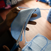 Sanitary pads are trimmed and stacked before being lined and sewn at the Afripads factory in the village of Kitengeesa in the Central Region of Uganda on 30 July 2014. Started by volunteers in 2009, Afripads manufactures reusable fibre sanitary pads made locally by community residents. Beginning with a single employee, the company now employs roughly 100 women and produces approximately 700 kits (consisting of pads, holders and a bag) each week. At USh 12,000 to 15,0000 (£2.75 to £3.40) for a kit that lasts approximately one year, Afripads offer a significant saving over disposables which may cost in excess of USh 42,000 (£9.60) over the course of a year. And for the many girls and women who cannot afford disposables, they offer an affordable and more hygienic alternative to rags, cotton wool or toilet paper, all of which are frequently used. At schools where Afripads have been distributed, teachers report that absenteeism has dropped sharply as girls who previously did not have access to proper sanitary pads now no longer stay home when they have their periods.