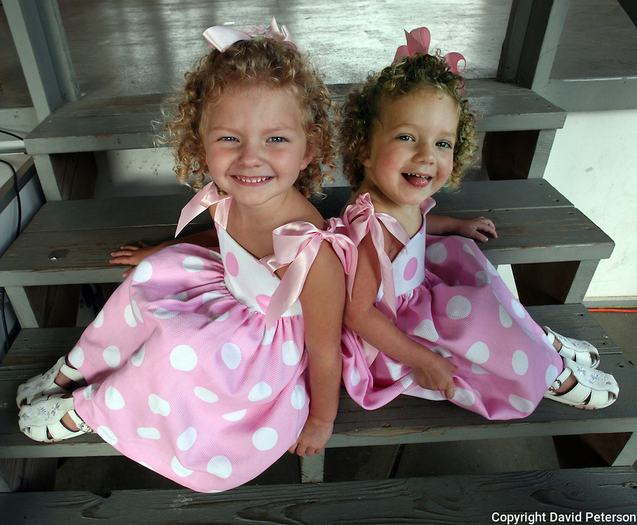 """Even though they are dressed alike, and have curly blond hair,  3-year-old twins Devon, left, and Darrah, from Pleasantville, Iowa, were entered in the """"least look alike"""" category of the Twins, Triplets and More Contest at the Iowa State Fair in Des Moines, Iowa in 2007."""