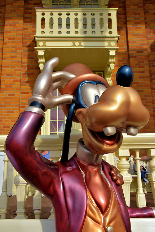 Goofy Statue on Main Street U.S.A. at Magic Kingdom in Orlando, Florida<br /> Outside of Tony&rsquo;s Town Square Restaurant on Main Street U.S.A. is this statue of Goofy. He is sitting on a bench decked out in a gold vest and hat, red tie and purple coat. Sit back and relax beside him. Have your photo taken. If you stay long enough, he may start talking to you. This lovable, two-toothed pooch was Dippy Dawg when he first appeared in &ldquo;Mickey&rsquo;s Revue&rdquo; in 1932. Since then, he has appeared in over 200 animated films and shorts.