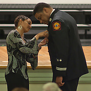 10/16/11 Wilmington DE: Captain Timothy F. Perkins has his wife pin his badge on him during Wilmington Fire Academy promotion Ceremony Monday, Oct. 17, 2011 at P.S. Dupont Middle school in Wilmington Delaware...Funding for 13 of the 14 members of the current class is coming from a controversial grant approved by City Council this past spring...The 13 men and one woman make up the 36th Wilmington Fire Department Academy, which will bring the department up to 173 members...The News Journal/SAQUAN STIMPSON