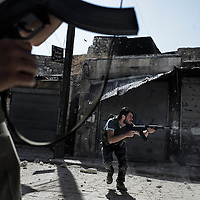 SYRIA, ALEPPO. A Syrian rebel fires toward regime forces in the Old City of Aleppo on September 24, 2012 ALESSIO ROMENZI