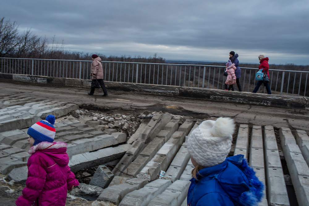 Bus passengers walk across a partially destroyed bridge on Thursday, February 11, 2016 between Artemivsk and Popasna, Ukraine. They were forced to get off the bus and walk for safety reasons so that the bus could pass over the bridge without passengers. They reboarded on the other side.