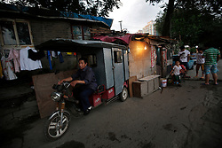A picture made available on 30 July 2013 of a Chinese tricycle rider parking his vehicle by his home in a slum or shanty town area by the second ring road of Beijing, a few hundred metres away from the prosperous Central Business District (CBD), separated only by a busy highway in China, 29 July 2013. Beijing announced plans to spend 500 billion yuan (61.5 billion euros) to renovate shanty towns within the fourth ring road according to local media. The five-year plan is expected to affect more than 230,000 households. China's massive urbanization push has resulted in the creation of large pockets of shanty towns and slums in urban areas as millions of migrant workers shifting to the cities are often priced out of city-centre properties. Slum or shanty town dwellers often live in dirty and cramped conditions, where they have no running water in their homes and have to share toilet and shower facilities.